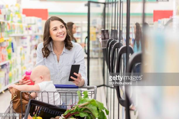 Cheerful young woman shops in frozen food section in supermarket