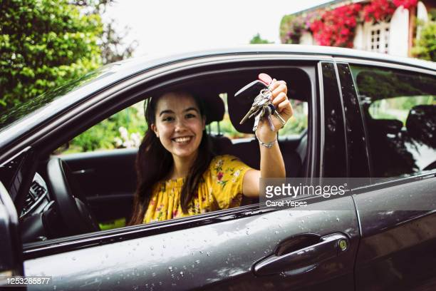 cheerful young woman showing the keys of her new car - new stock pictures, royalty-free photos & images