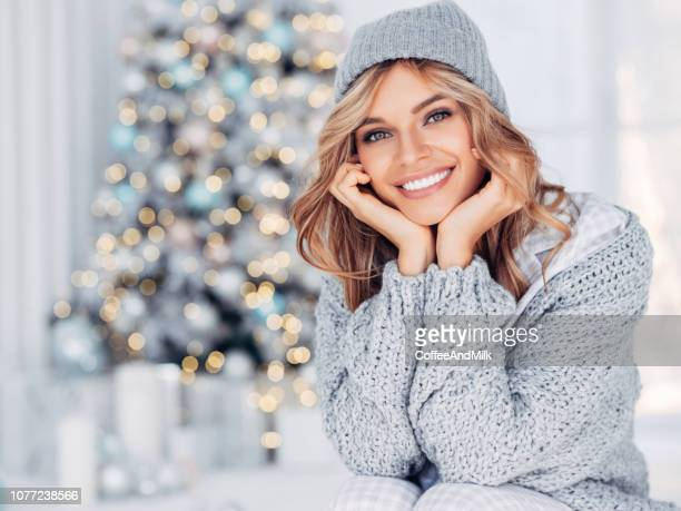 cheerful young woman sitting near christmas tree - sorriso aperto foto e immagini stock