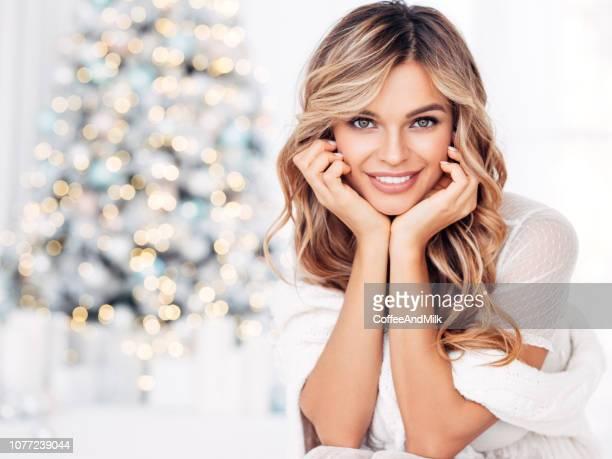 cheerful young woman sitting near christmas tree - pessoas bonitas imagens e fotografias de stock