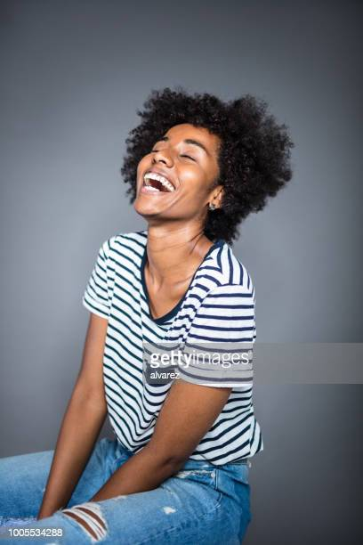 Cheerful young woman sitting with eyes closed
