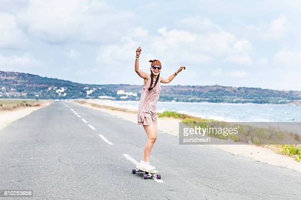 Cheerful young woman skateboarding on road next to the sea
