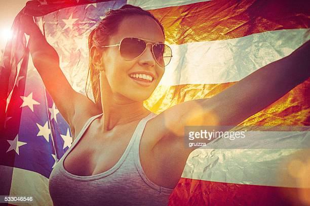 Alegre mujer joven parado en un prado sosteniendo bandera estadounidense