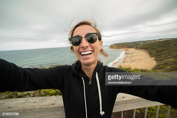 Cheerful young woman takes a selfie portrait on Bells Beach