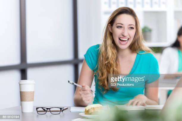 cheerful young woman takes notes during book club discussion - book club meeting stock pictures, royalty-free photos & images
