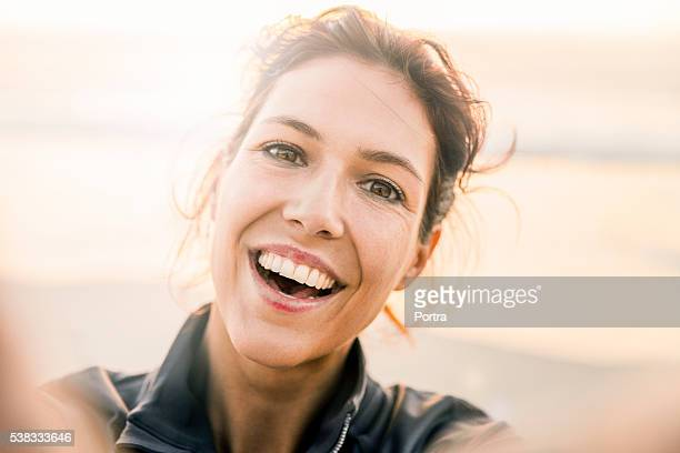 Cheerful young woman taking selfie at beach