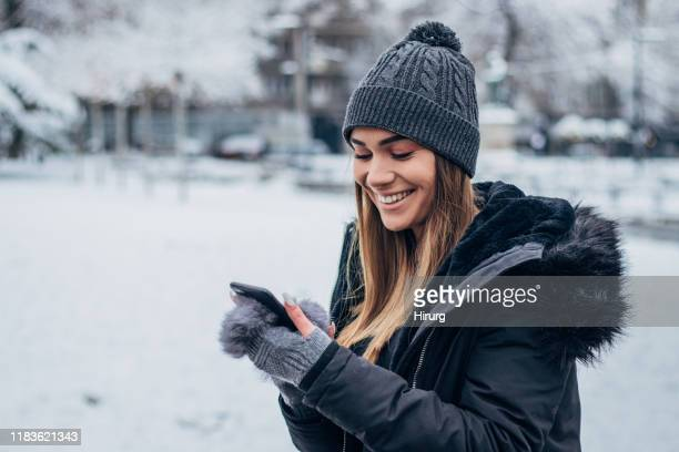 cheerful young woman text messaging - winter coat stock pictures, royalty-free photos & images