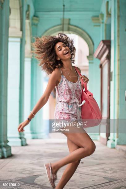 Cheerful young woman tossing hair at corridor