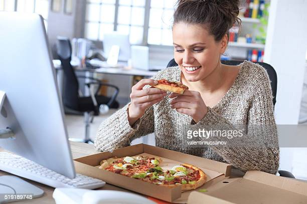 Cheerful young woman try to eat pizza at the office