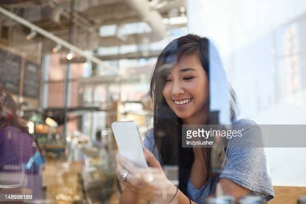 Cheerful young woman uses smartphone in cafe