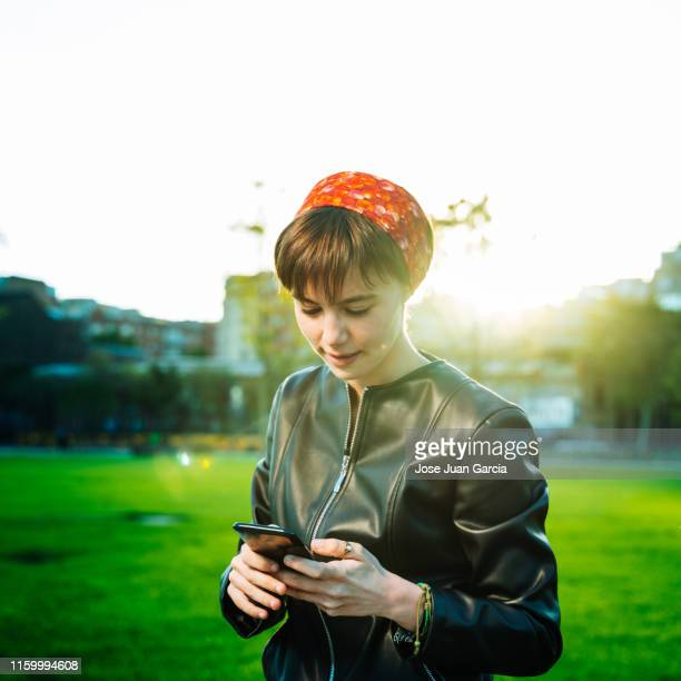cheerful young woman using phone in a park - western europe stock pictures, royalty-free photos & images