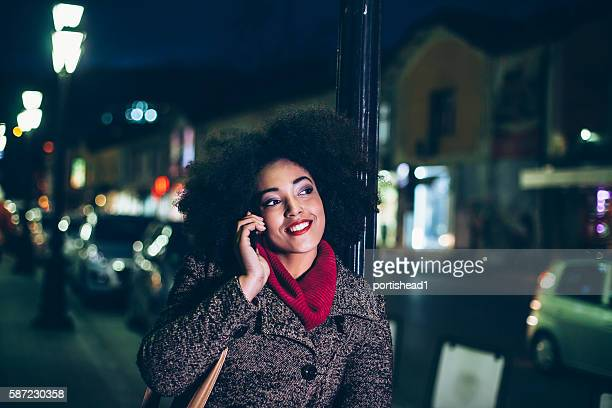 Cheerful young woman using phone on street by night