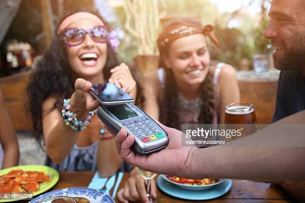 Cheerful young woman using smart phone for mobile payment