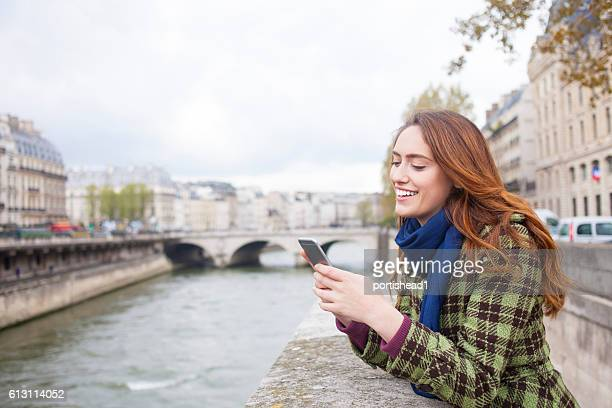 Cheerful young woman using smart phone on a bridge