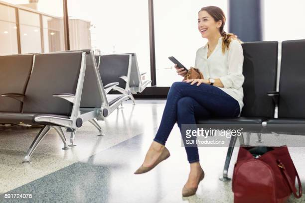 Cheerful young woman waits for flight at airport
