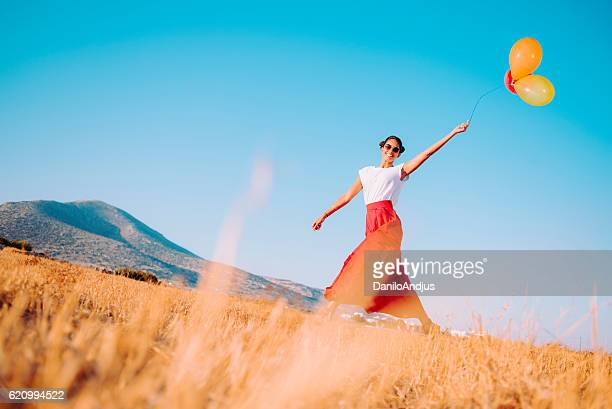 cheerful young woman walking in the field holding balloons