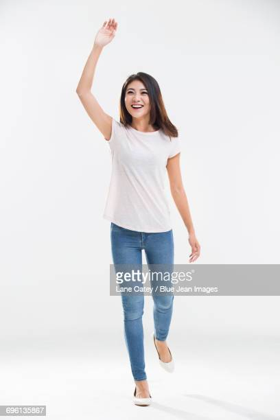 Cheerful young woman waving
