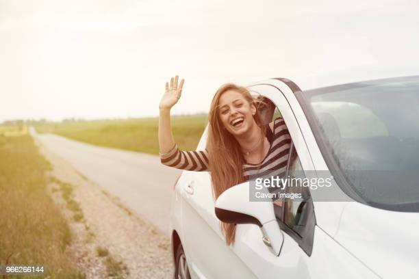 cheerful young woman waving while peeking from car window on country road - waving stock pictures, royalty-free photos & images