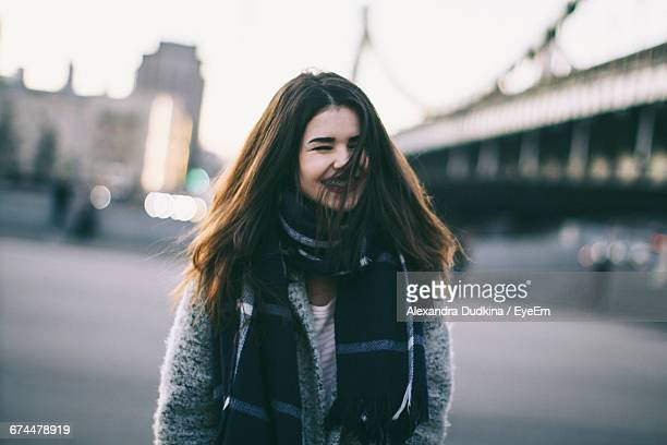 Cheerful Young Woman Wearing Scarf Standing On Street During Winter