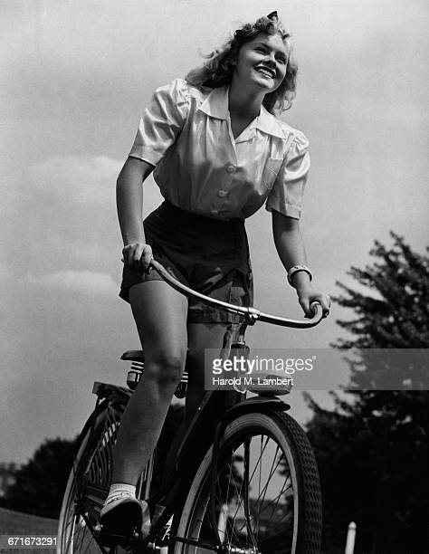 cheerful young woman wearing school uniform riding on bicycle - number of people stock pictures, royalty-free photos & images