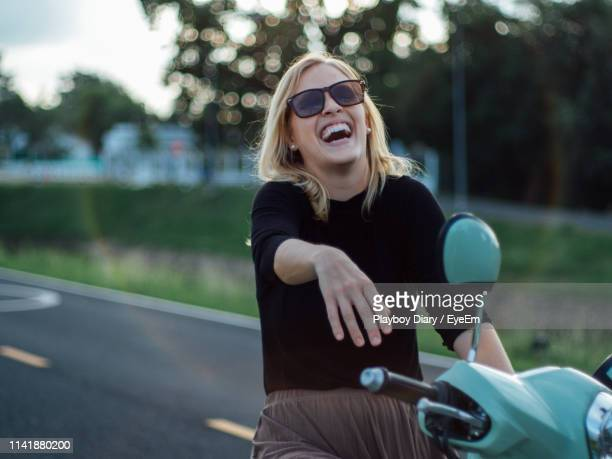 Cheerful Young Woman Wearing Sunglasses Sitting On Motor Scooter