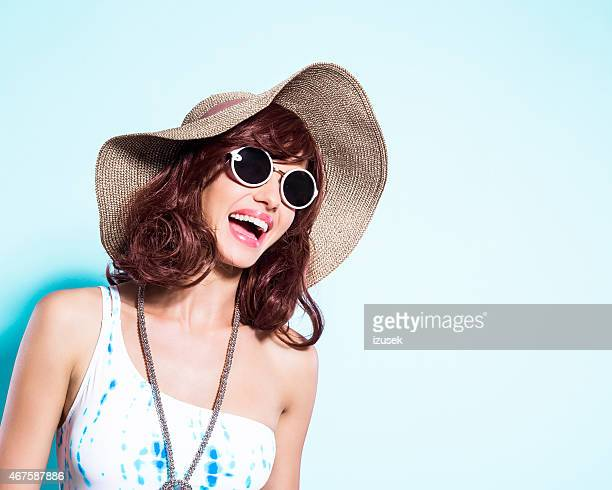Cheerful young woman wearing swimsuit and sun hat
