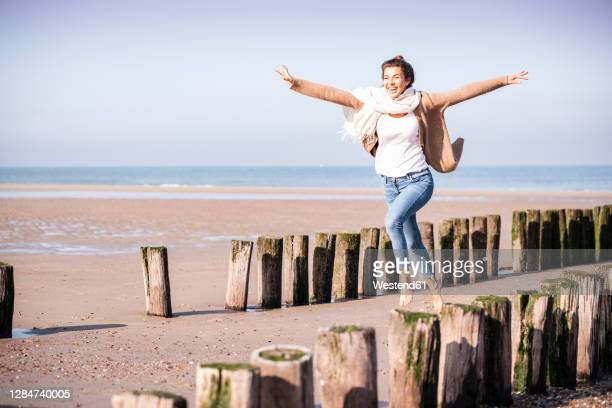 cheerful young woman with arms outstretched running amidst wooden posts at beach during sunny day - arms outstretched stock pictures, royalty-free photos & images