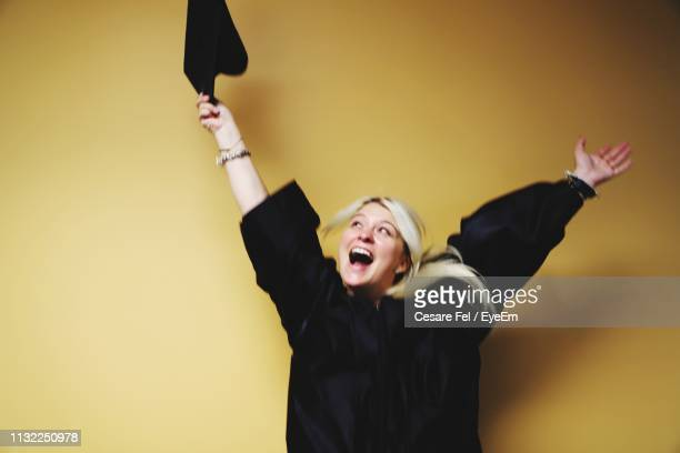 cheerful young woman with arms raised standing in graduation gown against yellow background - graduation background stock pictures, royalty-free photos & images