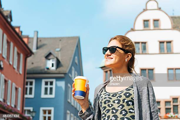cheerful young woman with cup of coffee sightseeing in city - drazen stock pictures, royalty-free photos & images