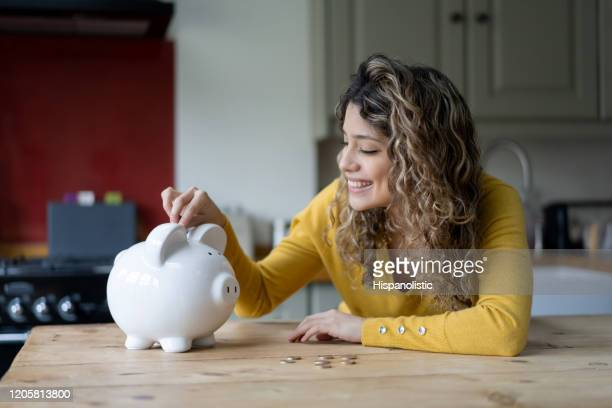 fröhliche junge frau mit lockigen haaren zu hause sparen münzen in ihr sparschwein - ersparnisse stock-fotos und bilder