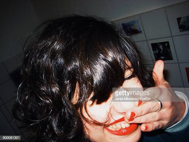 Cheerful young woman with orange lipstick and nail varnish