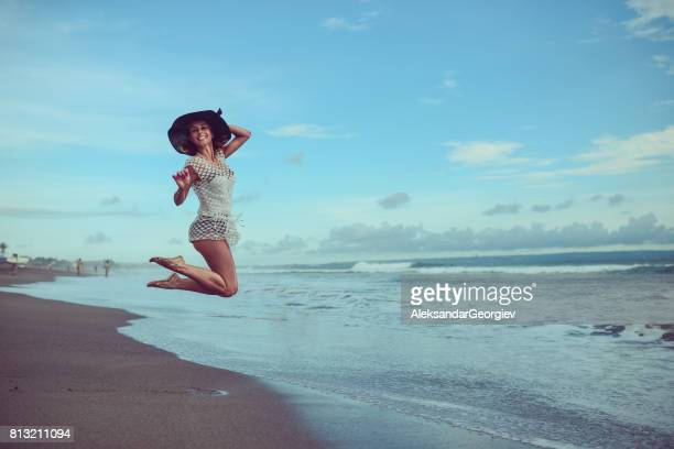 Cheerful Young Woman with Straw Hat Jumping at the Beach