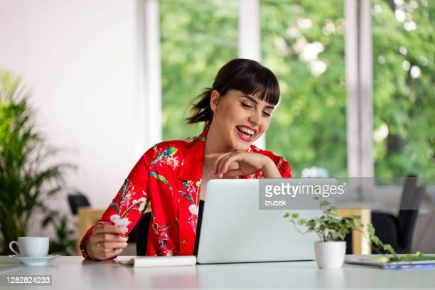 cheerful young woman working in the eco-friendly green office - red stock pictures, royalty-free photos & images
