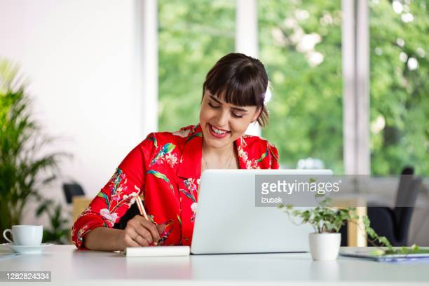 cheerful young woman working in the eco-friendly green office - working stock pictures, royalty-free photos & images