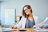 Cheerful young woman working with laptop and documents