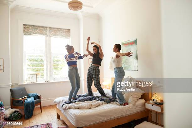 cheerful young women dancing on bed at home - ダンス ストックフォトと画像