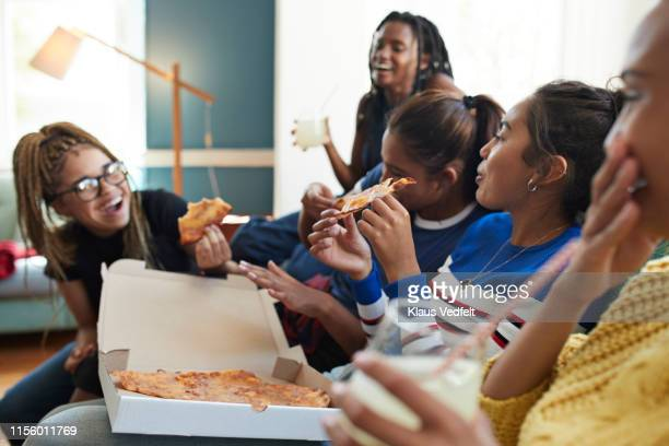 cheerful young women eating fresh pizza - weekend activities stock pictures, royalty-free photos & images