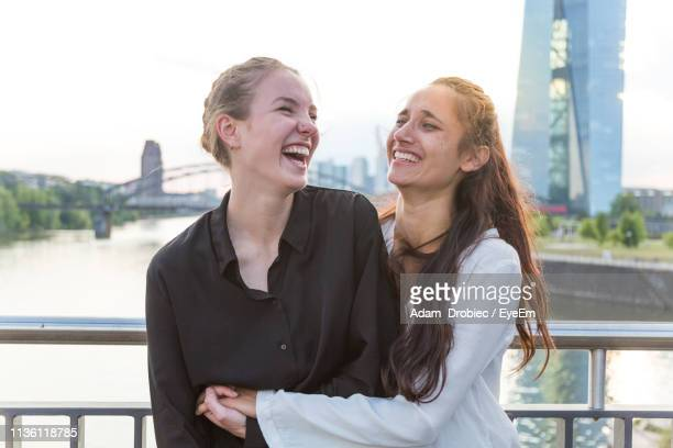 cheerful young women embracing while standing against railing on bridge in city - ヘッセン州 ストックフォトと画像