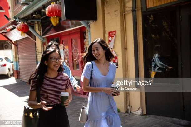 Cheerful young women enjoying city walk