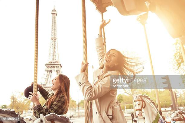 Cheerful young women having fun on carousel at Eiffel tower
