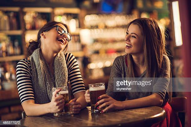 Cheerful young women laughing and drinking beer in a bar.