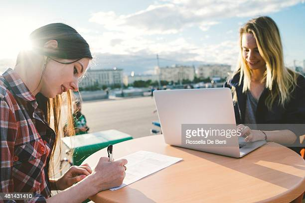 Cheerful Young Women Working In Coffee Shop Outdoors