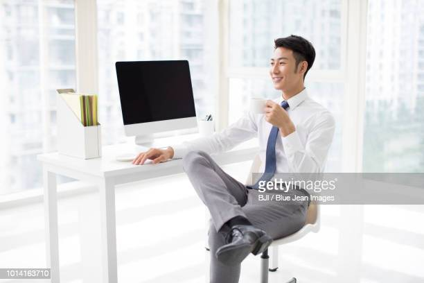 cheerful youngbusinessman taking a coffee break - 足を組む ストックフォトと画像