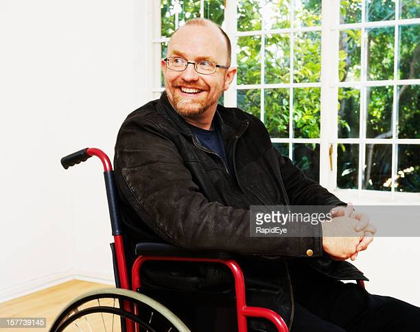 Cheerful-looking mature man sitting in wheelchair smiles over shoulder