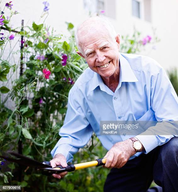 Cheerfully active 90-year-old man smilingly works in his garden