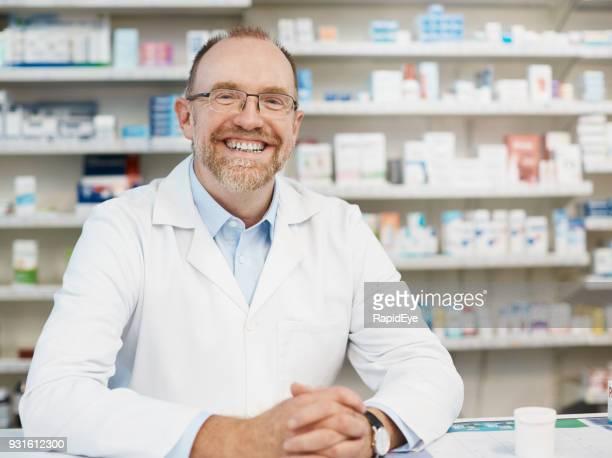 sorrindo alegremente farmacêutico masculino em pé atrás do balcão de farmácia - coat - fotografias e filmes do acervo