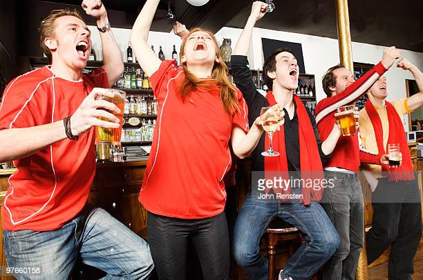 cheering at world cup on television in pub bar - supporter stock pictures, royalty-free photos & images