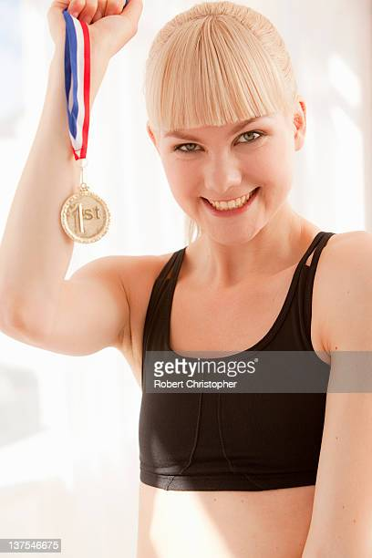 Cheering athlete holding gold medal