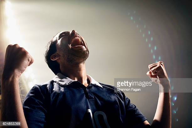 cheering athlete in stadium at night - camisa de futebol - fotografias e filmes do acervo