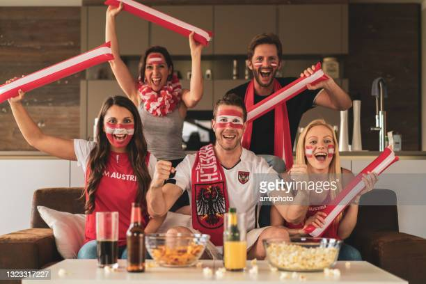 cheering austrian soccer fans watching live match at home - final game stock pictures, royalty-free photos & images